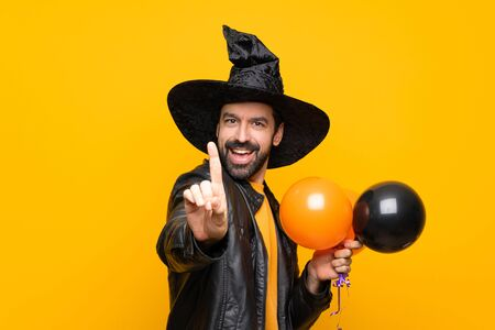Man with witch hat holding black and orange air balloons for halloween party showing and lifting a finger