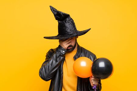 Man with witch hat holding black and orange air balloons for halloween party with tired and sick expression