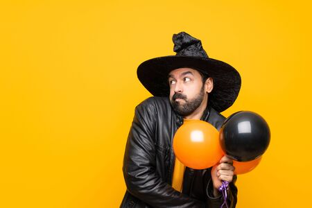 Man with witch hat holding black and orange air balloons for halloween party making doubts gesture while lifting the shoulders