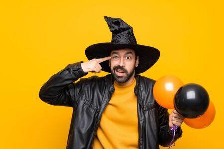 Man with witch hat holding black and orange air balloons for halloween party making the gesture of madness putting finger on the head