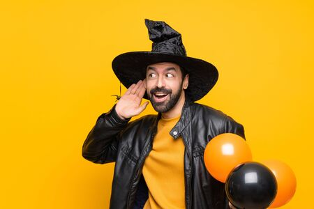 Man with witch hat holding black and orange air balloons for halloween party listening to something by putting hand on the ear Stok Fotoğraf