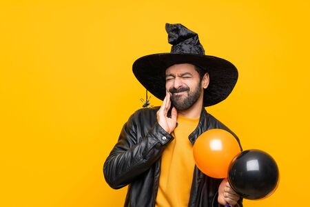Man with witch hat holding black and orange air balloons for halloween party with toothache