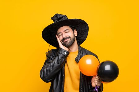 Man with witch hat holding black and orange air balloons for halloween party making sleep gesture in dorable expression 版權商用圖片