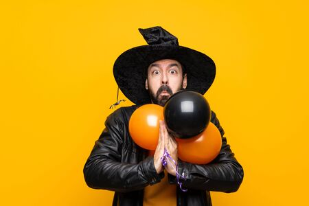 Man with witch hat holding black and orange air balloons for halloween party keeps palm together. Person asks for something