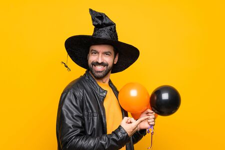 Man with witch hat holding black and orange air balloons for halloween party pointing to the side to present a product Imagens