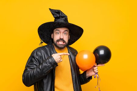 Man with witch hat holding black and orange air balloons for halloween party frightened and pointing to the side