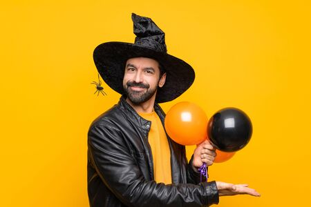 Man with witch hat holding black and orange air balloons for halloween party presenting an idea while looking smiling towards Imagens