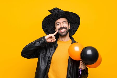 Man with witch hat holding black and orange air balloons for halloween party smiling with a happy and pleasant expression