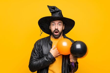 Man with witch hat holding black and orange air balloons for halloween party surprised and shocked while looking right