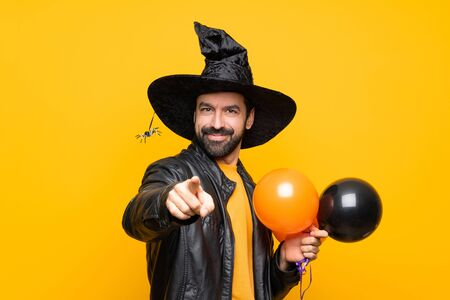Man with witch hat holding black and orange air balloons for halloween party points finger at you with a confident expression