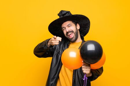 Man with witch hat holding black and orange air balloons for halloween party points finger at you while smiling