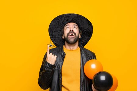 Man with witch hat holding black and orange air balloons for halloween party surprised and pointing up