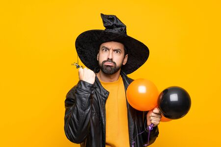 Man with witch hat holding black and orange air balloons for halloween party with angry gesture