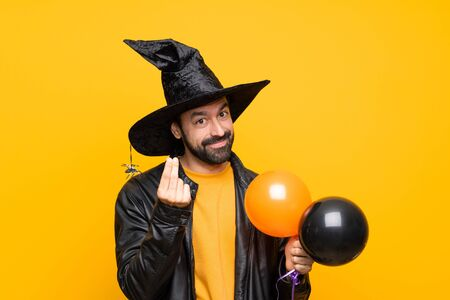 Man with witch hat holding black and orange air balloons for halloween party making money gesture Banco de Imagens