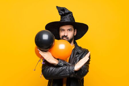 Man with witch hat holding black and orange air balloons for halloween party making NO gesture Фото со стока