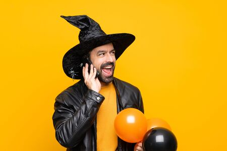 Man with witch hat holding black and orange air balloons for halloween party keeping a conversation with the mobile phone Stock Photo