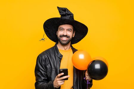Man with witch hat holding black and orange air balloons for halloween party sending a message with the mobile