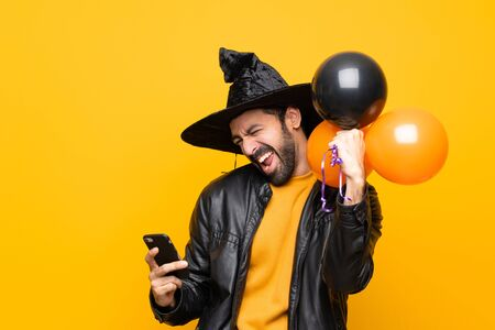 Man with witch hat holding black and orange air balloons for halloween party with phone in victory position Stock Photo