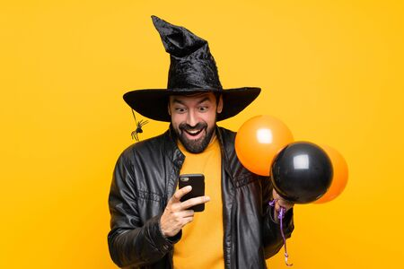 Man with witch hat holding black and orange air balloons for halloween party surprised and sending a message
