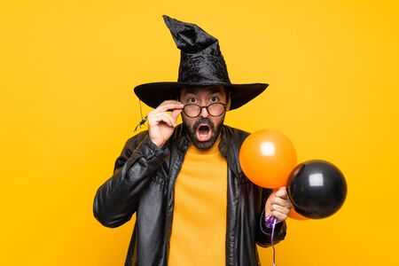 Man with witch hat holding black and orange air balloons for halloween party with glasses and surprised