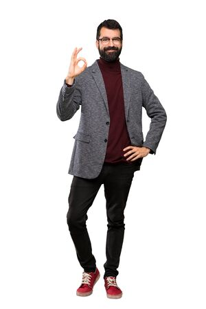Handsome man with glasses showing ok sign with fingers over isolated white background