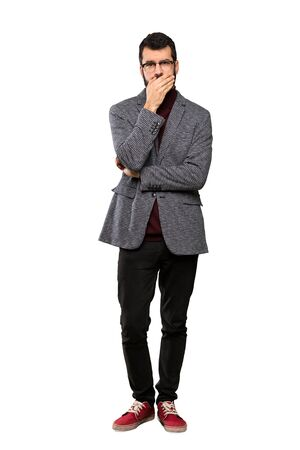 Handsome man with glasses covering mouth with hands over isolated white background