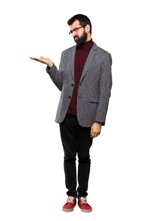 Handsome man with glasses holding copyspace with doubts over isolated white background Stok Fotoğraf