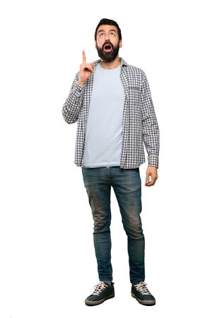 Handsome man with beard pointing up and surprised over isolated white background