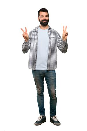 Handsome man with beard showing victory sign with both hands over isolated white background