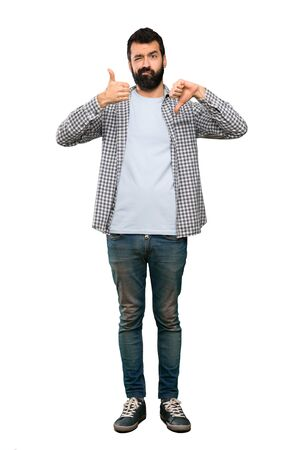 Handsome man with beard making good-bad sign. Undecided between yes or not over isolated white background