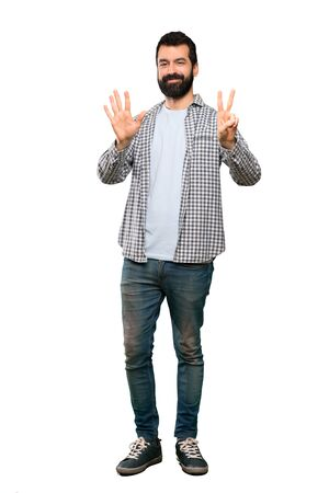 Handsome man with beard counting seven with fingers over isolated white background