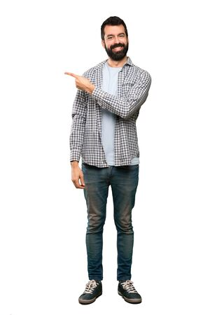 Handsome man with beard pointing to the side to present a product over isolated white background