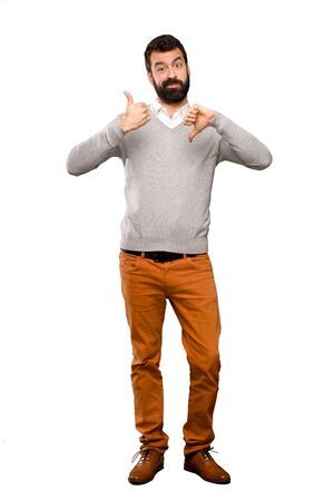 Handsome man making good-bad sign. Undecided between yes or not over isolated white background