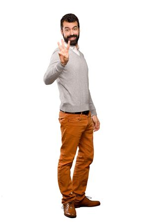 Handsome man happy and counting three with fingers over isolated white background Stock Photo