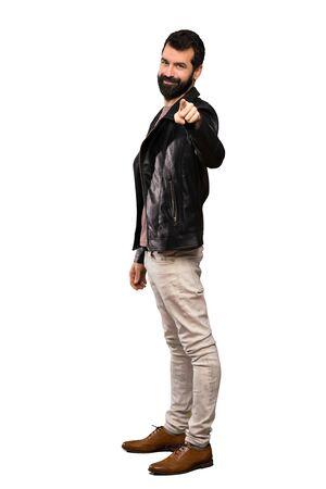 Un bell'uomo con la barba punta il dito contro di te con un'espressione sicura su sfondo bianco isolato