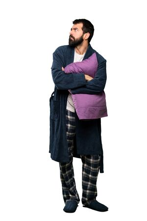 Man with beard in pajamas with confuse face expression over isolated white background Zdjęcie Seryjne - 131714012