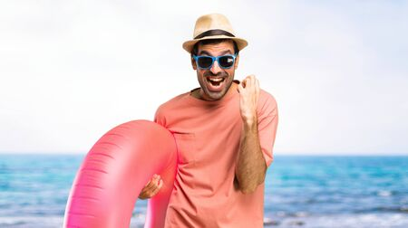 Man with hat and sunglasses on his summer vacation annoyed angry in furious gesture. Frustrated by a bad situation at the beach