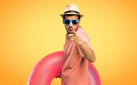Man with hat and sunglasses on his summer vacation annoyed angry in furious gesture. Frustrated by a bad situation and pointing to the front on orange background