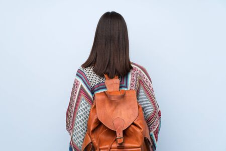 Young woman over isolated blue wall with backpack Banco de Imagens