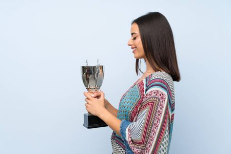 Young woman over isolated blue wall holding a trophy Stok Fotoğraf