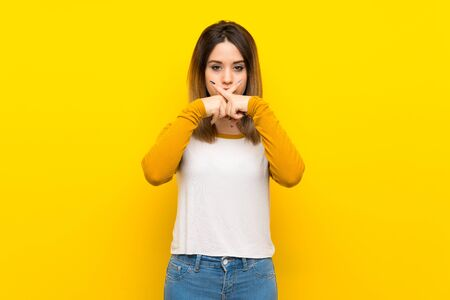 Pretty young woman over isolated yellow wall showing a sign of silence gesture