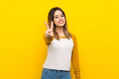 Pretty young woman over isolated yellow wall smiling and showing victory sign