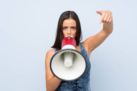 Young woman over isolated blue wall shouting through a megaphone Imagens - 131927793