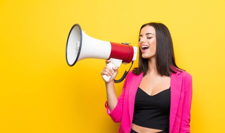 Young woman over isolated yellow background shouting through a megaphone Imagens - 131928582