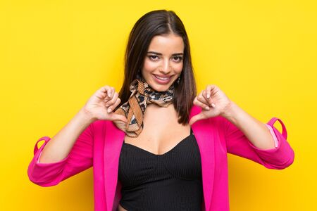Young woman over isolated yellow background proud and self-satisfied