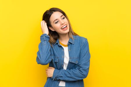 Young woman over yellow background laughing Stock fotó
