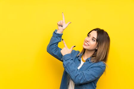Young woman over yellow background pointing with the index finger a great idea