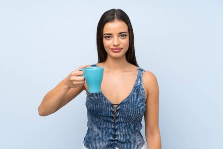 Young woman over isolated blue wall holding hot cup of coffee
