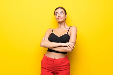 Young woman over isolated yellow background making doubts gesture while lifting the shoulders