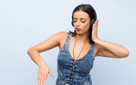 Young woman over isolated blue wall listening to music with headphones
